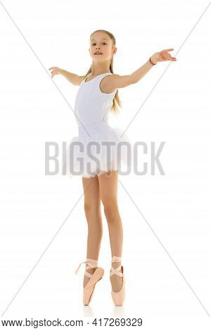 Cute Little Girl In A Tutu And Pointe Shoes Dancing In The Studio On A White Background.