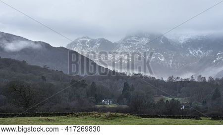 Stunning Landscape Image Of View From Elterwater Across Towards Langdale Pikes Mountain Range On Fog