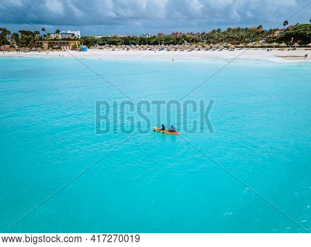 Couple Kayaking In The Ocean On Vacation Aruba Caribbean Sea, Man And Woman Mid Age Kayak In Ocean B