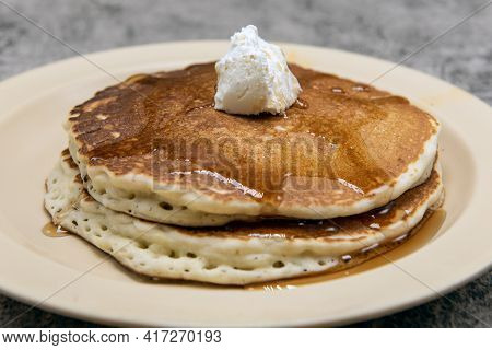 Short Stack Of Pancakes Dripping With Maple Syrup And Topped With Whipped Butter.