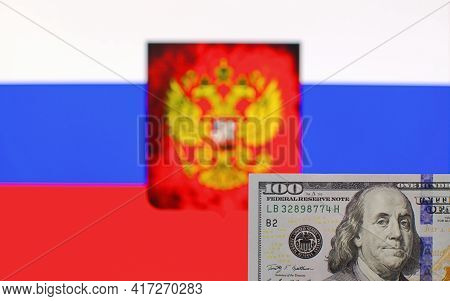 100 Us Dollars Banknote Close Up On Blurred Background Of Russian Federation Flag And Coat Of Arm