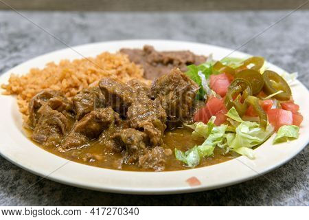 Authentic Mexican Food Plate Of Chili Verde Pork Smothered In Green Sauce Served With Refried Beans