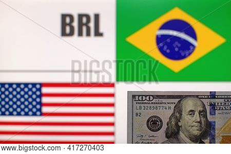 100 Us Dollars Banknote On Blurred Background Of Brazil And Usa Flags And Currency Code Of Brazil. E