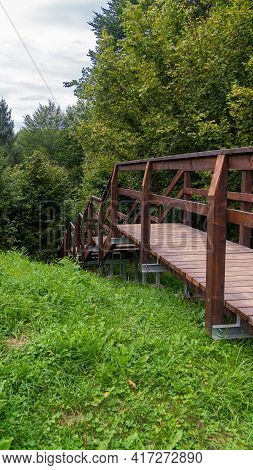 Very Clean And Modern Outdoor Wooden Stair On Downhill In Forest Vertical