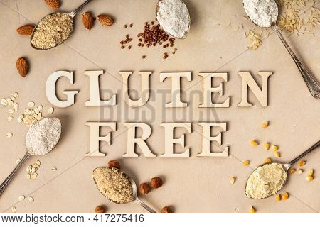 Metal spoons of various gluten free flour (almond, oatmeal, buckwheat , rice, corn) and gluten free lettering made of wooden letters