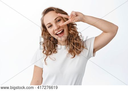 Young Positive Woman With Blond Curly Hair, Natural Make Up, Smiling Happy And Showing V-sign, Peace