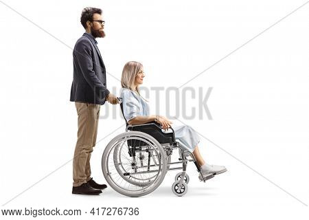 Full length profile shot of a bearded man pushing a young woman patient in a wheelchair isolated on white background