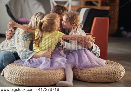 A young happy family in a hug while playing in a cheerful atmosphere at home together. Family, home, playing, togetherness