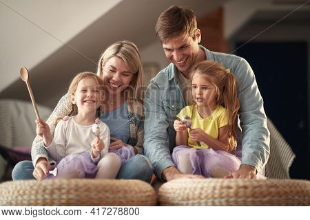 A young happy family enjoying drumming on the furniture in a cheerful atmosphere at home. Family, home, playing, togetherness