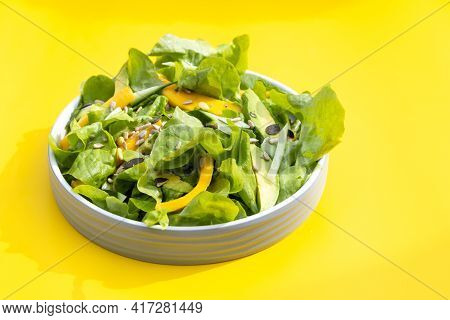 Salad With Mango, Avocado, Cucumber, Lettuce And Seeds On Yellow Background .home Made, Tasty Food.