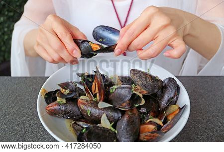 Woman Having Her Steamed Mussels In White Wine By Using An Empty Mussel Shell To Grab Another Mussel