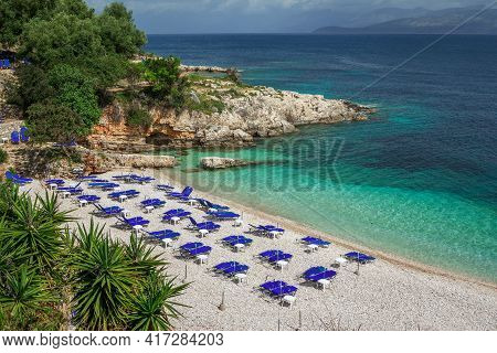View Of Empty Beach - Blue Deck Chairs And Umbrellas Near Sea Water, Cliffs And Rocks, Green Trees A