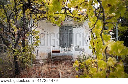 Old Baby Bed Against A Wall Of Abandoned Traditional House In Mediterranean Garden Framed With Yello