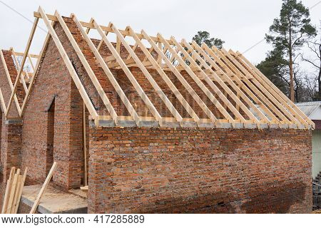 Installation Of Wooden Beams At Construction The Roof Truss System Of The Brick House. Mauerlat Lyin