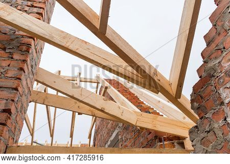 Installation Of Wooden Beams At Construction The Roof Truss System Of The Brick House.