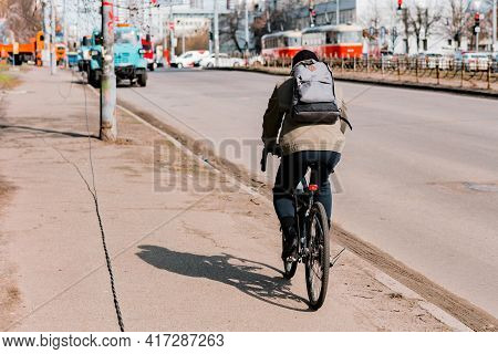Man Cycling Through The City's Pavement In A Jacket With Grey Back Pack. Cold Weather. Sidewalk. Urb