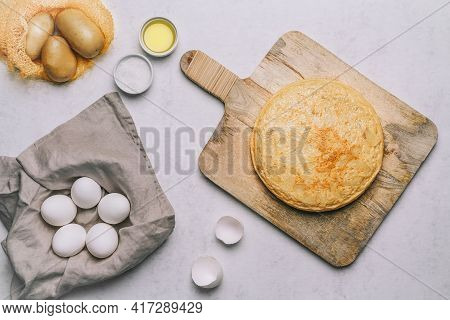 Aerial View Of A Potato Omelette On A Retro Wooden Table, A Basket Of White Eggs, Olive Oil And Salt