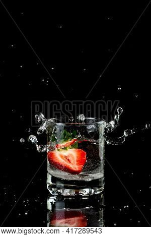 Half A Strawberry Fell Into A Glass Of Water. Strawberry Water On A Black Background. Splash. Copy S
