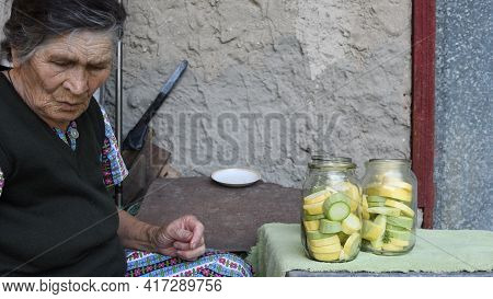 Wrinkled Senior Asian Woman Looks Down While Sitting Near Table With Glass Jars Of Sliced Raw Zucchi