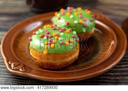 Bun, Donut Covered With Glaze. Tutti Frutti Bun On A Plate. Sweet Pastries. Dessert. Still Life. Clo