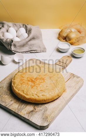 Potatoes Omelette On A Rustic Wooden Table, A Basket Of White Eggs, Olive Oil And Salt And An Orange