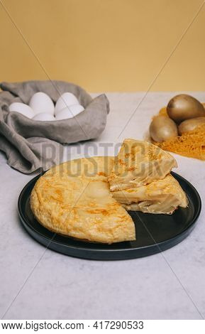 Potatoes Omelette With A Triangle Portion Cut Into A Black Round Plate On A Yellow Background And A