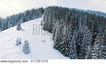 Breathtaking Winter Scenery Of Snow Covered Evergreen Forest With Mountains In The Background During