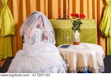 Jewish Bride In A Lush White Dress, Her Face Covered With A Veil, Crying Before The Chupa Ceremony D