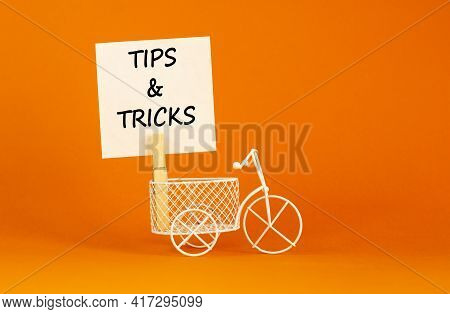 Tips And Tricks Symbol. White Paper. Words 'tips And Tricks'. Miniature Bicycle. Beautiful Orange Ba