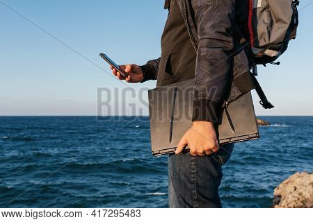 Unrecognizable Person With Backpack Using His Smartphone And With His Laptop In Hand. Digital Nomad