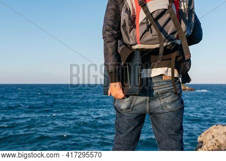 Person With A Backpack On His Back And With A Laptop In His Hand Observing The Sea On The Coast. Dig