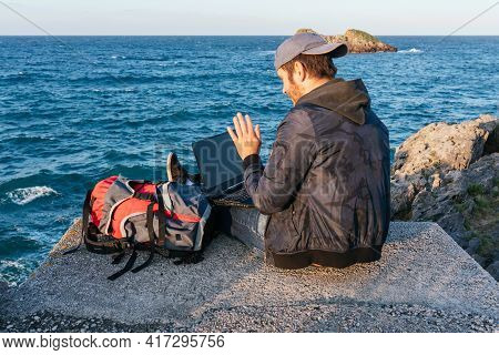 Young Nomadic Traveler Using His Laptop To Make A Video Call With His Family In Front Of The Sea. Bu