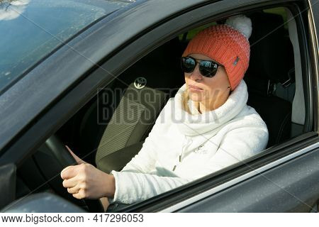 Dnepropetrovsk, Ukraine - 08.04.2021: Portrait Of A Beautiful Woman Driving A Car. The Woman Often T