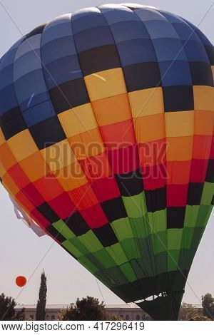 Blue, Orange, Yellow, Green Are The Colors Of A Huge Parachute. The Parachute Is In The Air.