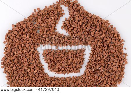 Instant Coffee Granules Lying On The Surface. A Cup Of Coffee Drawn On The Surface Of Scattered Dry