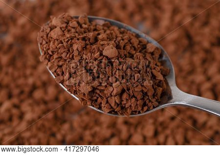 Instant Coffee Granules Lying On The Surface. The Spoon Contains Dry Granules Of Instant Coffee.