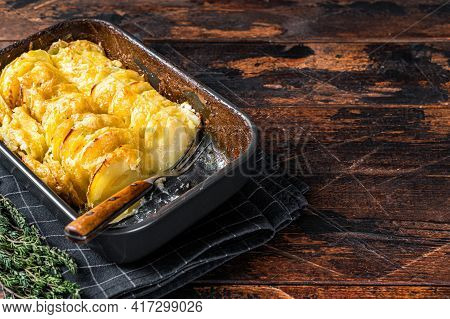 Potato Casserole Gratin Dauphinois In A Baking Dish. Dark Wooden Background. Top View. Copy Space