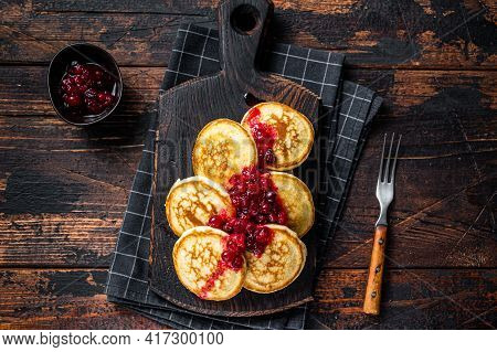 Stack Of Cranberry Syrup Pancakes On Wooden Board. Dark Wooden Background. Top View