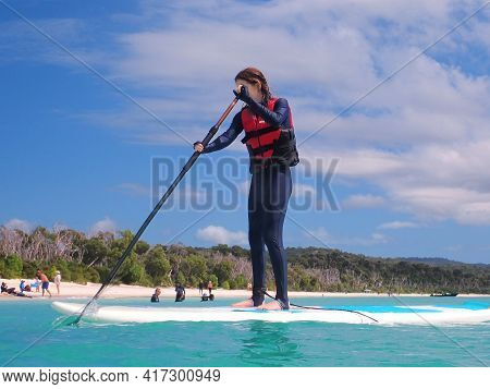 Whitehaven Beach, Whitsundays, Queensland, Australia - April 2021: Young Woman Standing On Paddle Bo