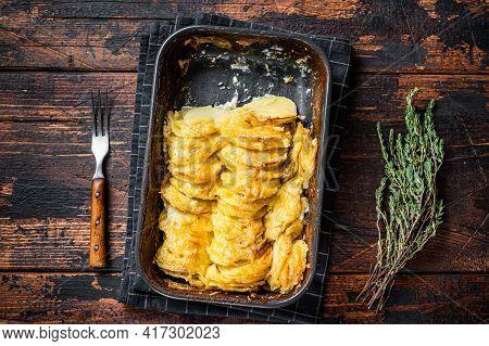 Potato Casserole Gratin Dauphinois In A Baking Dish. Dark Wooden Background. Top View