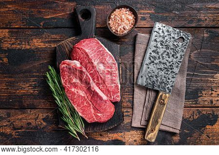 Uncooked Raw Shoulder Top Blade Or Flat Iron Beef Meat Steaks On A Wooden Butcher Board With Meat Cl