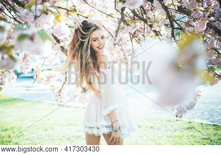 Spring Girl In Short Pink Dress Enjoying Sunny Day In Garden. Female Playing With Long Gorgeous Blon