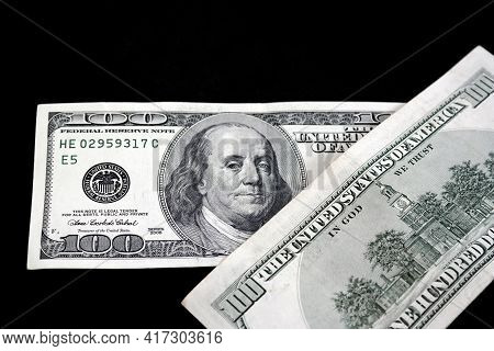100 Us Dollars On A Black Background, The World Market And 100 Usd Gaining Value,