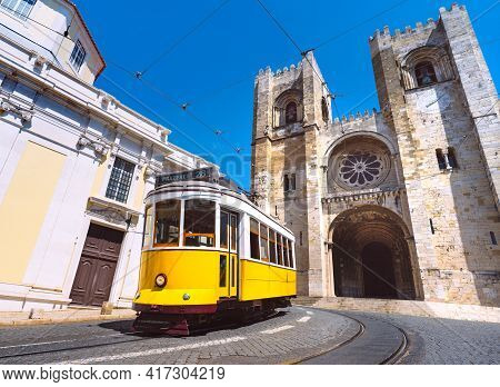 Lisbon City Old Town And Famous Yellow Tram 28 In Front Of Santa Maria Cathedral On A Sunny Summer D