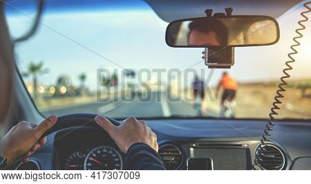 Group Of Professional Cyclists Training On Highway With Safety Escort Car. A Group Of Cyclists Follo