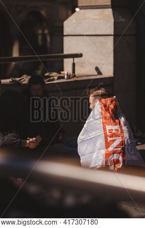 Westminster, London | Uk -  2021.04.17: Homeless Man Wearing The Flag Of England As A Cape Sitting W