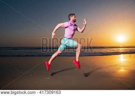 Man Running On The Beach At Sunset. Guy Runner Jogger Running. Dynamic Jumping Movement. Sport Jump.