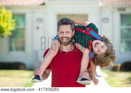 Parent Supports And Motivates Son. Father Giving Son Piggyback Ride After Come Back From School.