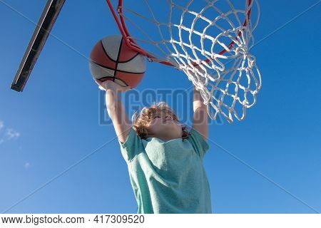 Closeup Portrait Of Kid Boy Basketball Player Making Slam Dunk During Basketball Game.