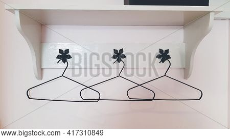 Three Clothes Or Coat Hanger Hanging On White Wall With Wooden Shelf On Top. Group Of Object And Des